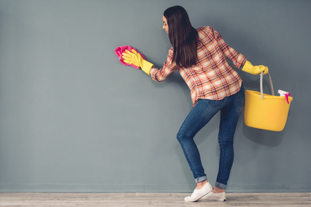 Beautiful young woman in protective gloves is cleaning a wall Standard-Bild