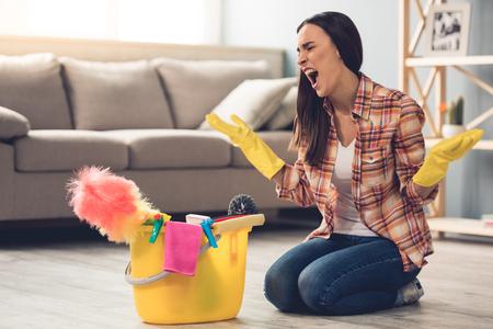 De mooie jonge vrouw in beschermende handschoenen zit boos dichtbij de emmer met dingen voor het schoonmaken terwijl het schoonmaken van haar huis