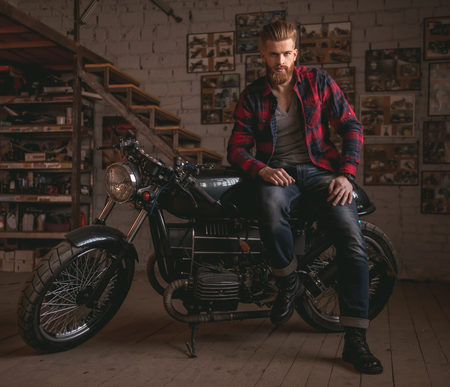 Handsome bearded man in stylish casual clothes is posing at camera while sitting on the motorcycle in the repair shop Stock fotó - 72772719
