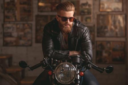 가죽 자 켓과 태양 안경에서 잘 생긴 수염 난된 남자가 수리 샵에서 오토바이에 앉아있다 스톡 콘텐츠