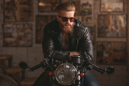 Handsome bearded man in leather jacket and sun glasses is sitting on the motorcycle in the repair shop Standard-Bild