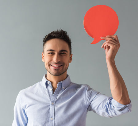 Attractive young man is holding a speech bubble, looking at camera and smiling, on gray background