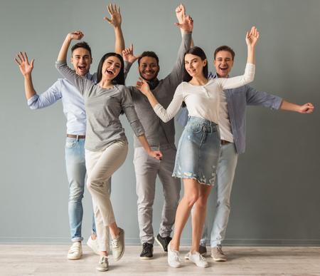 Schöne junge Menschen in Freizeitkleidung heben die Hände in die Kamera schaut und lächelnd, auf grauem Hintergrund photo