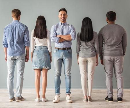 In voller Länge Portrait der schönen jungen Menschen in einer Reihe stehen, den Rücken gekehrt, um Kamera, ein Kerl Kamera blickt und lächelt photo
