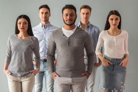 Schöne junge Menschen in ungezwungener Kleidung Blick in die Kamera, auf grauem Hintergrund photo