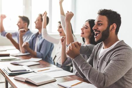 Schöne intelligente Schüler heben die Hände zu Fäusten und lächelt, während er in der Klasse sitzen photo