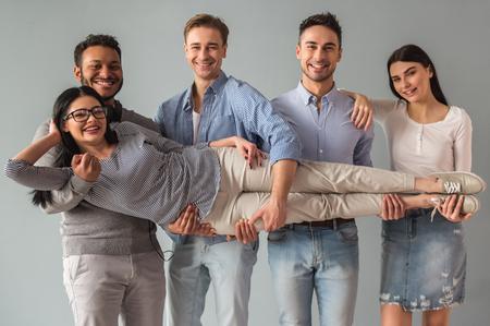 Schöne junge Leute in der beiläufigen Kleidung halten ein Mädchen in die Kamera schaut und lächelnd, auf grauem Hintergrund photo