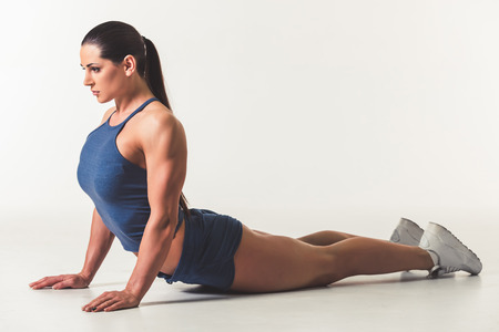 Beautiful strong woman in sportswear is stretching, on light background Stock Photo - 73417571