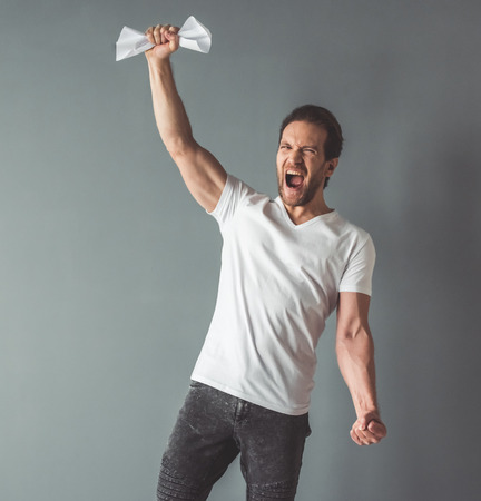 Handsome man is grasping paper and screaming, on gray background