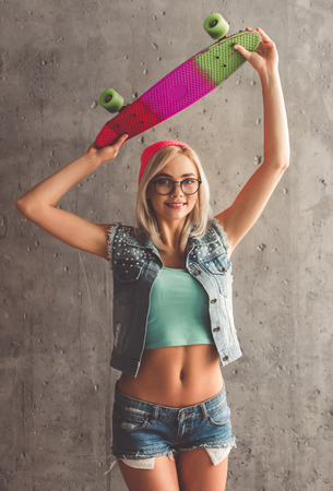 Stylish young girl in jean clothes is holding a skateboard, looking at camera and smiling, on concrete wall background