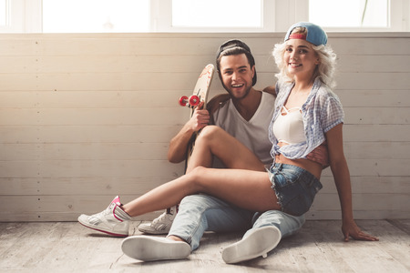 Stylish young couple in caps is looking at camera and smiling while sitting on the floor