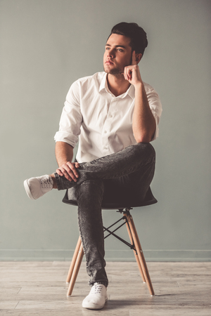 Stylish young man is looking away while sitting on chair on gray background