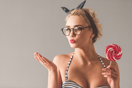 Stylish young girl in summer clothes is holding a lollipop and sending air kiss, on gray background Stock Photo