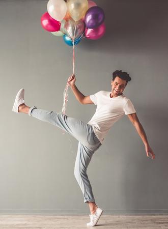 El hombre joven divertido está sosteniendo los globos y está sonriendo mientras que salta en fondo gris Foto de archivo - 73435504