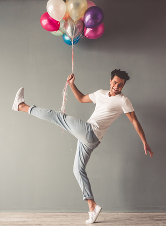 saltar: Funny young man is holding balloons and smiling while jumping on gray background Foto de archivo