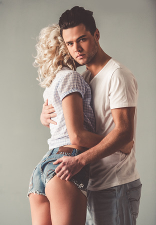 Portrait of stylish young couple hugging, on gray background Фото со стока