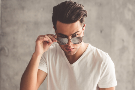 Stylish young man is looking at camera from under sun glasses, on concrete wall background