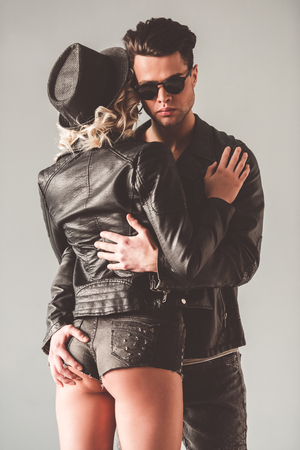 Portrait of stylish young couple in leather jackets and glasses hugging, on gray background