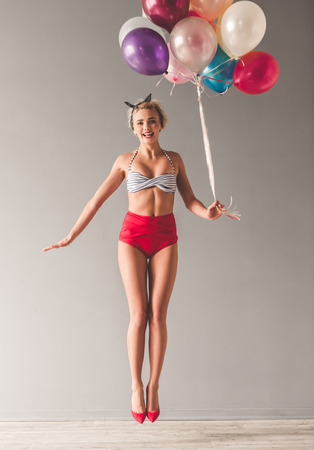 Full length portrait of stylish young girl in summer clothes holding balloons, jumping and smiling, on gray background