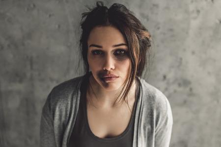 女の子は打たれます。灰色の背景にカメラ見て悲しいことに彼女の顔のあざを持つ少女の肖像画
