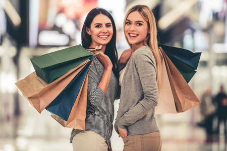 Beautiful girls with shopping bags are looking at camera and smiling while doing shopping in the mall Stock Photo