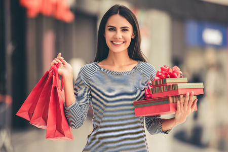 Beautiful girl is holding shopping bags and gift boxes, looking at camera and smiling while standing in the mall