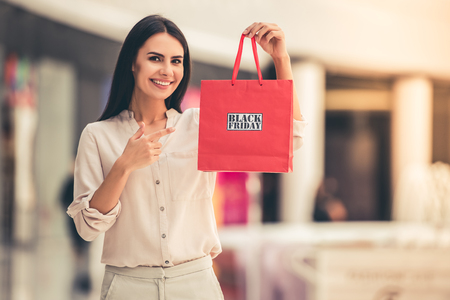Beautiful girl is holding shopping bag with phrase Black friday, looking at camera and smiling while standing in the mall