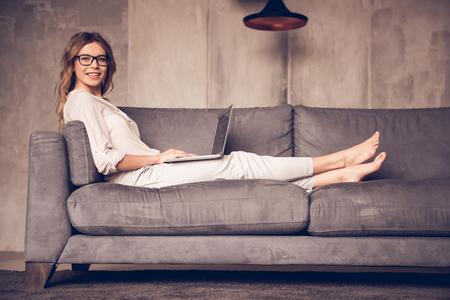 カジュアルな服と眼鏡で美しいビジネス女性のラップトップを使用して、カメラ目線と自宅のソファに腰掛けながら笑顔