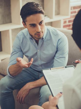 잘 생긴 젊은 남자가 심리학자의 소파에 앉아있는 동안 자신의 문제에 대해 이야기하고있다.