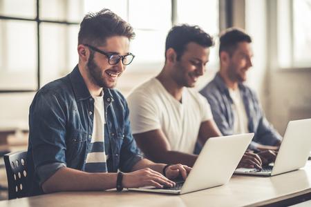 Drei gut aussehenden Geschäftsleute sind mit Laptops und lächelnd, während die im Büro arbeiten photo