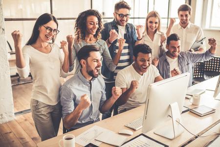 Erfolgreiche junge Geschäftsleute heben die Hände in den Fäusten und mit Glück schreien, während mit einem Computer im Businesscenter arbeiten photo