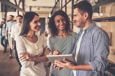 Erfolgreiche junge Geschäftsleute werden mit einer digitalen Tablette und lächelt, während im Business Center steht photo