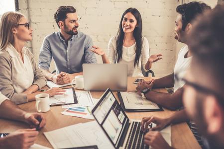Erfolgreiche junge Geschäftsleute verwenden Gadgets, Dokumente diskutieren und während der Konferenz lächelnd photo