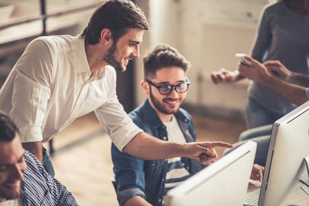 Erfolgreiche junge Geschäftsleute sind mit Laptops, reden und lächelnd, während die im Büro arbeiten photo