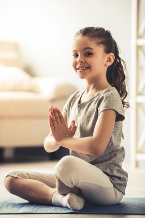 Charmantes kleines Mädchen schaut in die Kamera und lächelt beim Yoga zu Hause