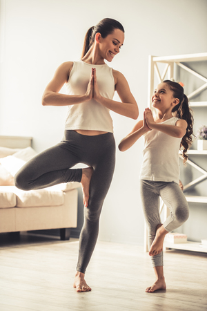 Beautiful young woman and charming little daughter are smiling while doing yoga together at home Фото со стока