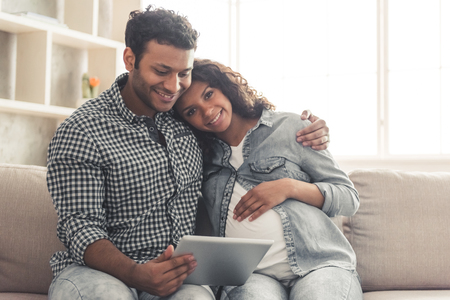 Handsome Afro American man and his beautiful pregnant wife are using a digital tablet and smiling while spending time together at home