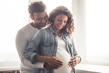 Handsome Afro American man and his beautiful pregnant wife are hugging and smiling while standing near the window at home Archivio Fotografico