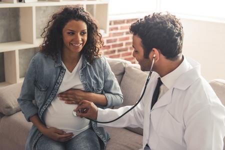 Gut aussehende afroamerikanischer Arzt im weißen Mantel berät schöne schwangere Frau in seinem Büro photo