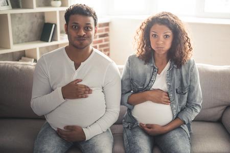 Gut aussehende afroamerikanischer Mann mit gefälschtem Bauch und seiner schönen schwangeren Frau hält die Hände auf ihrem Bauch photo
