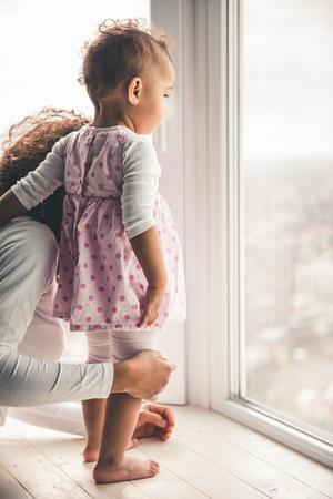 Schöne junge Afro American Mutter und ihr süßes Baby suchen aus dem Fenster photo