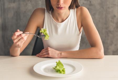 섭식 장애. 양상추를 먹는 여자 자른 이미지