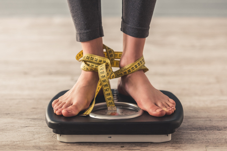Cropped image of woman feet standing on weigh scales, on gray background. Legs winded with a tape measure Stock Photo
