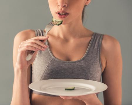 Eetstoornis. Bebouwd beeld van meisje die een plaat met een plak van komkommer op het houden, geïsoleerd op wit