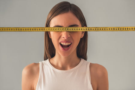 Suffering from anorexia. Portrait of girl with a tape measure in front of her eyes, on gray background