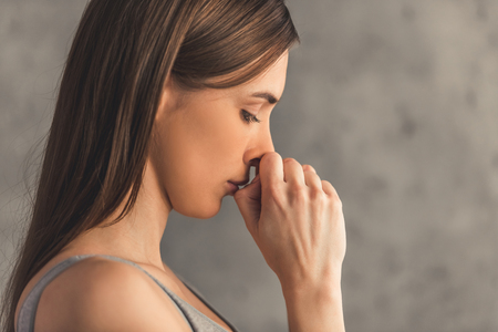Suffering from anorexia. Side view of sad girl looking down