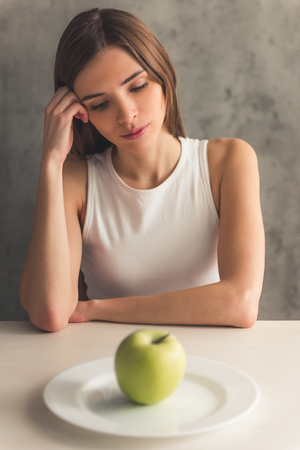 Eating disorder. Girl is sitting in front of the plate with an apple and looking at it Archivio Fotografico