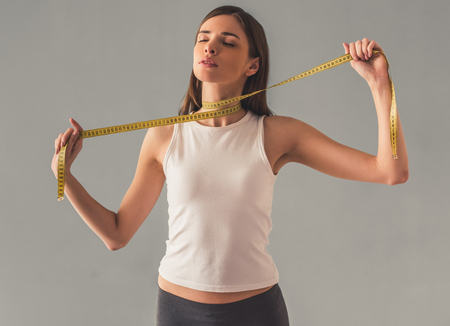 Suffering from anorexia. Girl holding a tape measure around her neck, on gray background