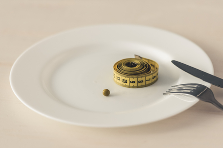 Weight loss concept. Plate with a tape measure on it