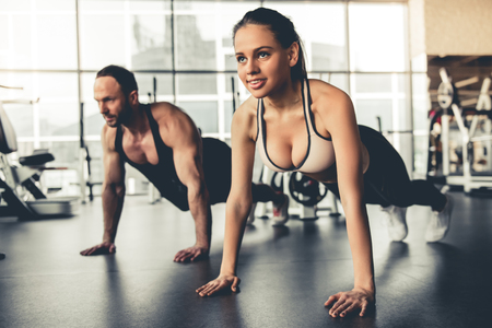 Attractive sports people are doing plank exercise while working out in gym
